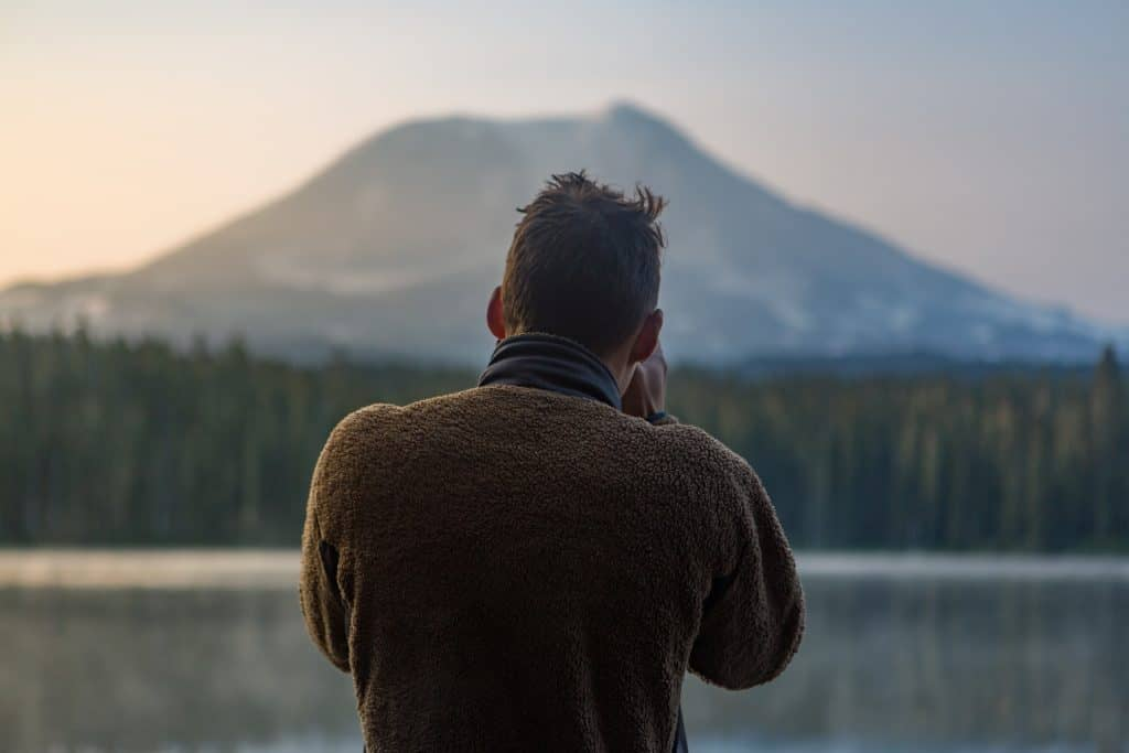 depth of field photography of man in gray sweater standing in front of mountain