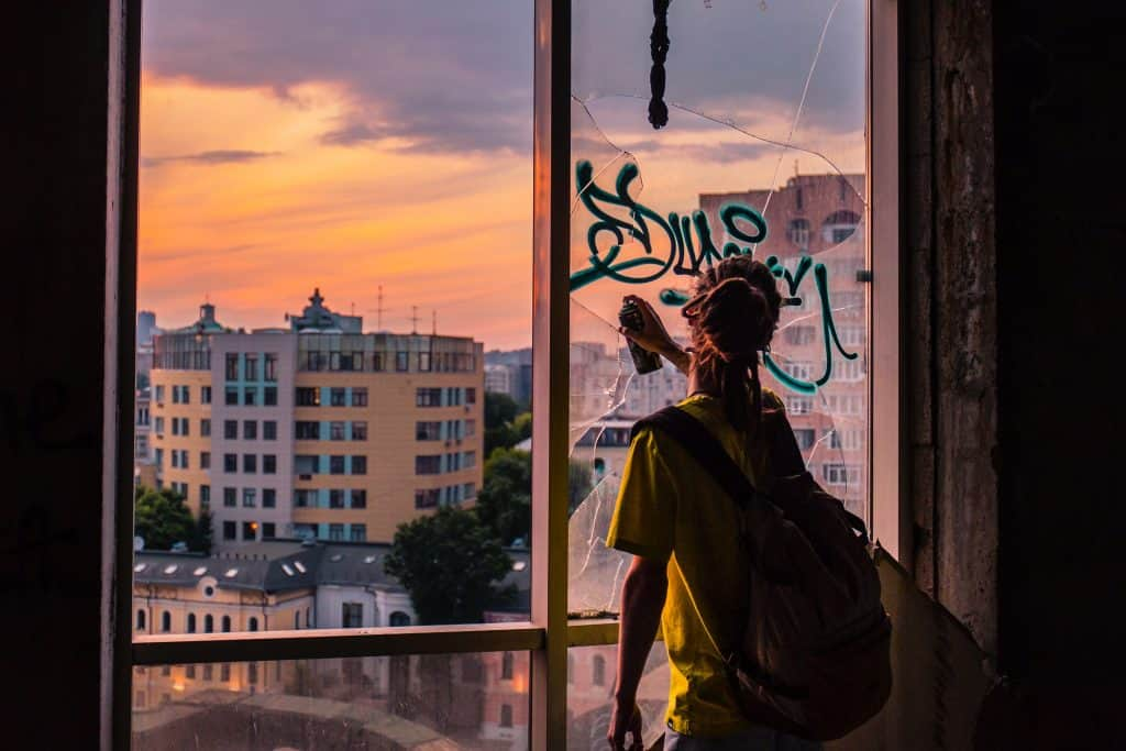 woman doing graffiti art in window glass