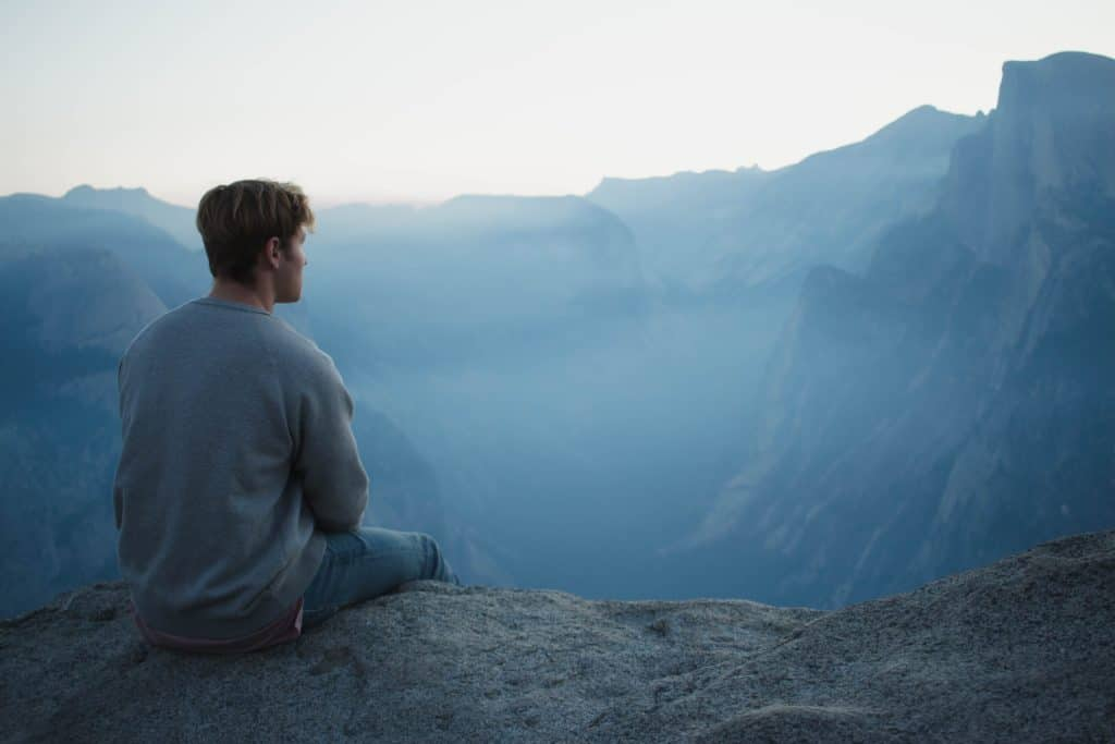 man in gray shirt sits on cliff