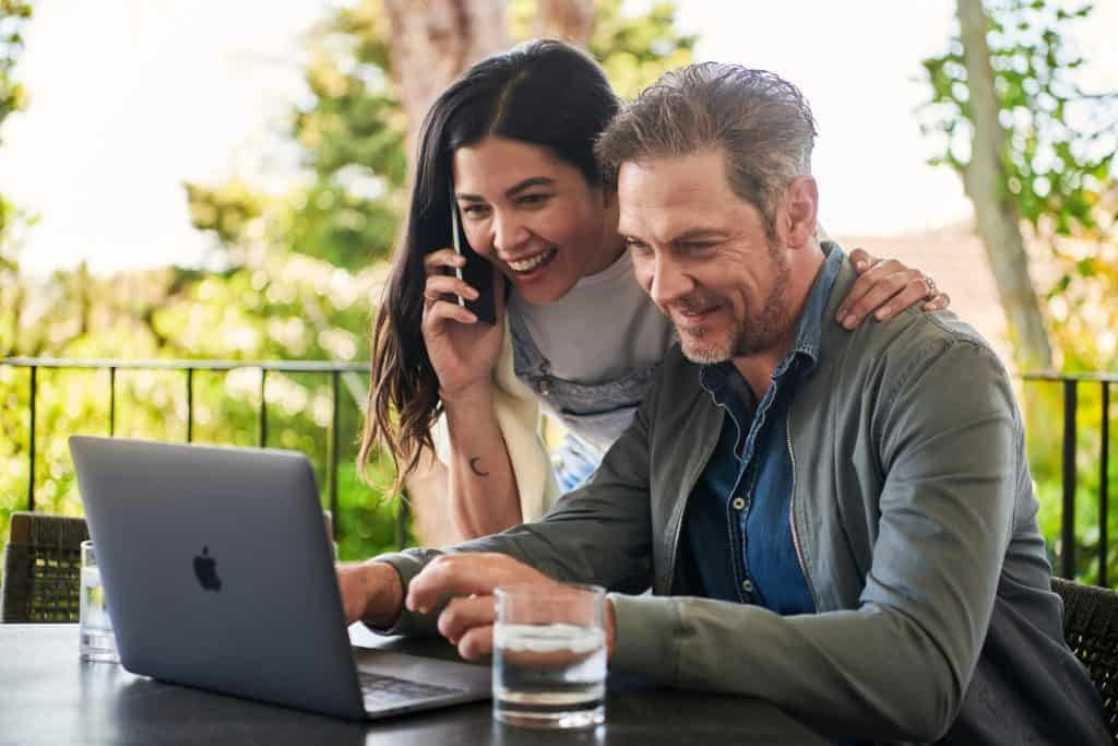 man sitting beside woman looking at laptop